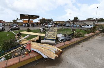 Bystanders gather next to wreckage at a damaged fuel station in Focene near Fiumicino, some 40km south-west of Rome on July 28, 2019, where an overnight tornado lifted a car driven by a 27 year-old woman  smashing it on the road killing her instantly. - Storms have struck much of central and northern Italy, killing two people while the south is experiencing hot weather. (Photo by Vincenzo PINTO / AFP)