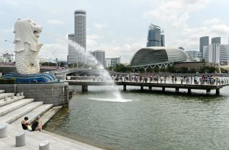 Tourists gather at Merlion park to take pictures overlooking Marina bay in Singapore on August 11, 2016. - Singapore on August 11 narrowed its economic growth forecast for this year, citing concerns over the weaker global outlook and the impact of Britain's vote to leave the EU. (Photo by ROSLAN RAHMAN / AFP)