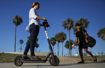 LOS ANGELES, CA - AUGUST 13: A woman rides a Bird shared dockless electric scooter along Venice Beach on August 13, 2018 in Los Angeles, California. Shared e-scooter startups Bird and Lime have rapidly expanded in the city. Some city residents complain the controversial e-scooters are dangerous for pedestrians and sometimes clog sidewalks. A Los Angeles Councilmember has proposed a ban on the scooters until regulations can be worked out.   Mario Tama/Getty Images/AFP