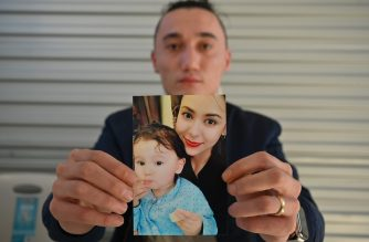 Sadam Abdusalam holds up a photo of his Uighur wife Nadila Wumaier and their baby son Lutifeier at a restaurent in Sydney's western suburbs on July 17, 2019. (Photo by PETER PARKS / AFP)