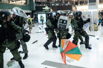 Police officers run as an umbrella is dropped by protesters during a clash inside a shopping arcade in Sha Tin of Hong Kong after a rally against a controversial extradition law proposal in Sha Tin district of Hong Kong on July 14, 2019. (Photo by Philip FONG / AFP)