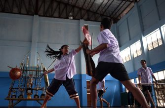 This photo taken on July 8, 2019 shows students practicing Krabi Krabong, a Thai martial art, at the Thonburee Woratapeepalarak school in Thonburi, on the outskirts of Bangkok. (Photo by Lillian SUWANRUMPHA / AFP)
