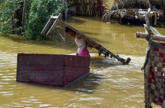A man carries furniture from his house at a flooded area during heavy monsoon rains in Karachi on July 31, 2019. - At least 12 people were killed as monsoon rains lashed Pakistan's port city of Karachi, officials and charity groups confirmed on July 31, while flooding also triggered power outages and overwhelmed the metropolis's fragile infrastructure. (Photo by ASIF HASSAN / AFP)