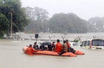 People are being rescued on a boat by personnel from the National Disaster Response Force (NDRF) as they pass by vehicles submerged floodwaters of Vadodara, some 110 kms from Ahmedabad on August 1, 2019. - The Vadodara city of Gujarat state got flooded due to very heavy rains on July 31, through water coming from Ajwa Dam and Vishwamitri river. (Photo by STR / AFP)