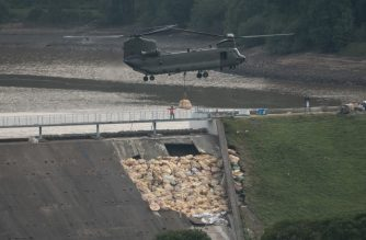 An RAF Chinook helicopter drops more bags of aggregate on the damaged section of spillway of the Toddbrook Reservoir dam above the town of Whaley Bridge in northern England on August 4, 2019. - Another 55 homes have been evacuated from an English town threatened by a collapsing dam, emergency services said Sunday as they raced to reduce the water levels ahead of fresh storms. (Photo by OLI SCARFF / AFP)