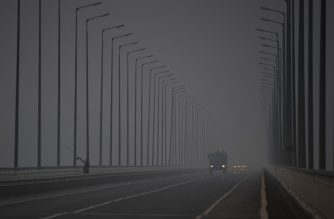 Cars drive on a bridge over the Angara river in smoke from forest fires outside the settlement of Boguchany on August 3, 2019. (Photo by Ekaterina ANISIMOVA / AFP)