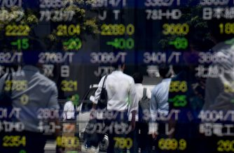 Pedestrians are reflected on an electronics stock indicator at the window of a securities company in Tokyo on August 6, 2019. - Tokyo stocks opened down nearly three percent on August 6, after Wall Street suffered the worst session of the year on worries about an escalating US-China trade war. (Photo by Toshifumi KITAMURA / AFP)