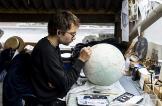 An artist applies paintwork to a globe at the Bellerby and Co Globemakers' workshop and headquarters in Stoke Newington in north London, on July 19, 2019. - In 2008, Peter Bellerby set out to buy his father a high quality handmade globe as an 80th birthday present. When he could not find one, the Briton decided to make it himself -- and, in the process, catapulted himself into a new profession. (Photo by Niklas HALLE'N / AFP)
