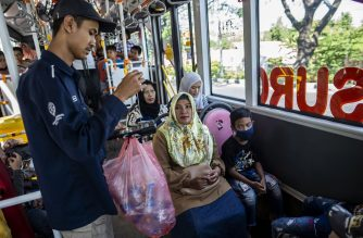This picture taken on July 21, 2019 shows a bus conductor collecting used plastic bottles as fare payment on board a Suroboyo bus in the Indonesian city of Surabaya. - Indonesia is the world's second-biggest marine polluter behind China and has pledged to reduce plastic waste in its waters some 70 percent by 2025 by boosting recycling, raising public awareness, and curbing usage. (Photo by Juni Kriswanto / AFP) / TO GO WITH Indonesia-environment-plastic,FEATURE by Harry PEARL