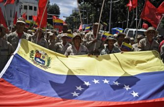 Pro-government protesters rally against US sanctions with a Venezuelan national flag in Caracas on August 7, 2019. - Washington warned China and Russia to avoid doing business with the Venezuelan regime of Nicolas Maduro, as delegates from some 60 countries discussed ways of ending the crisis in the South American nation. The admonition Tuesday came a day after President Donald Trump ordered a freeze on all Venezuelan government assets in the United States and barred transactions with its authorities. (Photo by Federico Parra / AFP)