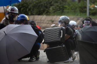 (FILES) This file photo taken on August 5, 2019 shows a protester (C) using a piece of luggage to shield himself as police fire tear gas in Wong Tai Sin during a general strike in Hong Kong, as simultaneous rallies were held across seven districts. - Hong Kong protesters who have taken to the streets for nearly two months are harnessing everything from traffic cones to kitchenware to battle tear gas as demonstrations escalate. (Photo by Isaac LAWRENCE / AFP) / TO GO WITH HongKong-politics-China-unrest-police,FOCUS