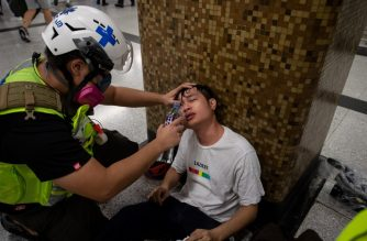 This picture taken early on August 4, 2019 shows a man taking refuge in an MTR underground station as he receives treatment after being affected by tear gas, as a protest takes place outside the station in the Wong Tai Sin area of Hong Kong's Kowloon district. - Nurses, doctors, medical students and ordinary people with first aid training have all clamoured to join what has become a small volunteer corps helping treat people on the frontlines of protests that have engulfed the city for over two months. (Photo by ANTHONY WALLACE / AFP) / TO GO WITH HongKong-politics-unrest-China-health,FOCUS by Yan Zhao