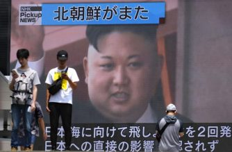 Pedestrians walk past a giant screen in Tokyo reporting about North Korea's missile launch earlier in the day, on August 10, 2019. - North Korea conducted the latest in a series of missile launches Saturday to protest US-South Korean war games, just hours after US President Donald Trump expressed his own frustration with the exercises. (Photo by Kazuhiro NOGI / AFP)