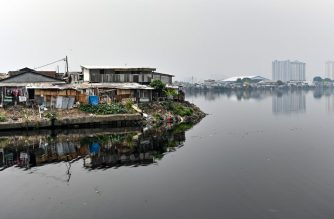 In this picture taken on July 5, 2019 public houses reach the edge of a reservoir in northern Jakarta. - Indonesia's capital is being swallowed into the ground at such an alarming rate that experts warn much of it could be submerged by 2050. (Photo by BAY ISMOYO / AFP) / TO GO WITH STORY: Indonesia-environment-social, by Dessy SAGITA