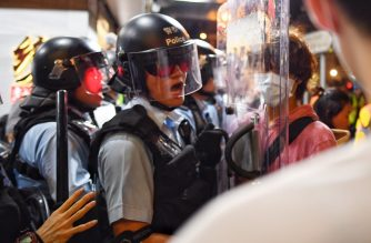 A Police man (L) shouts at a Pro-Democracy Protestor (R) to move out of his way during a gathering in the Sham Shui Po Area of Hong Kong on August 14, 2019. - More than 10 weeks of sometimes-violent demonstrations have wracked the semi-autonomous city, with millions taking to the streets to demand democratic reforms and police accountability. (Photo by Manan VATSYAYANA / AFP)