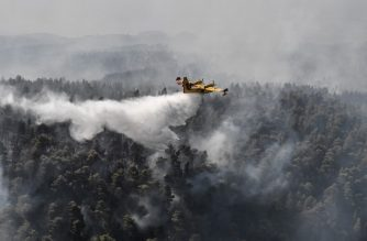 """A Canadair firefighting plane makes a water drop near Kontodespoti village on the island of Evia, northeast of Athens, on August 14, 2019. - Hundreds of villagers were evacuated on August 13 and the Greek prime minister cancelled a vacation as scores of firefighters battled a major wildfire on the country's second-largest island of Evia, authorities said. """"Conditions are exceptionally difficult and the state's first priority is to protect lives,"""" Greek prime minister told reporters outside the fire department's centre of operations, after cutting short a vacation on his home island of Crete. Four Canadair fire-fighting planes from Croatia and Italy would be deployed on August 14 after Greece requested EU assistance. (Photo by LOUISA GOULIAMAKI / AFP)"""