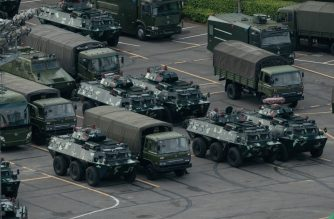 Trucks and armoured personnel carriers are seen parked at the Shenzhen Bay stadium in Shenzhen, bordering Hong Kong in China's southern Guangdong province, on August 16, 2019. - Chinese military personnel and armoured personnel carriers have mustered in large numbers across the border in Shenzhen, as Hong Kong's pro-democracy movement faces a major test this weekend as it tries to muster another huge crowd following criticism over a recent violent airport protest and as Beijing ramps up its bellicose threats. (Photo by STR / AFP)