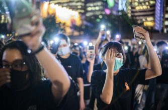 Secondary school students cover their right eye as they hold up their phone torches while attending a rally at Edinburgh Place in Hong Kong on August 22, 2019. - Hong Kong student leaders on Thursday announced a two-week boycott of lectures from the upcoming start of term, as they seek to keep protesters on the streets and pressure on the government. (Photo by Anthony WALLACE / AFP)