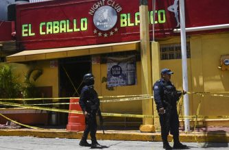"""Police officers stand guard outside Caballo Blanco bar (White Horse bar) on August 28, 2019 where at least 26 people were killed and 11 badly wounded on the eve after gunmen trapped revellers inside the Caballo Blanco bar (White Horse bar) and started a raging fire. - President Andres Manuel Lopez Obrador condemned the """"shameful"""" attack and said federal authorities would investigate evidence it may have stemmed from collusion between local authorities and organized crime. (Photo by Pedro PARDO / AFP)"""