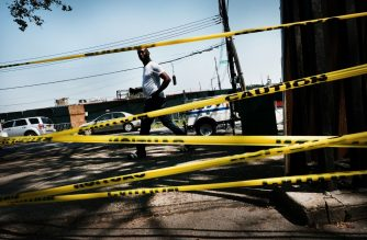 NEW YORK, NEW YORK - JULY 29: A man walks by police tape in the Brownsville neighborhood in Brooklyn where one person was shot and killed and 11 others were injured after two or more shooters opened fire during a massive block party on July 29, 2019 in New York City. Gunfire erupted during an annual community celebration, the Old Timers Event, which was being held at a playground and park. While crime has gone down in New York City overall, certain sections of Brooklyn have witnessed a spike in shootings and murders. Police are still looking for the shooters.   Spencer Platt/Getty Images/AFP