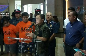 The PNP presents two of the three suspects who were arrested for allegedly attempting to extort money from lawmakers, including Senator Bong Go, on Thursday, Aug. 1, as the senator speaks to the media./Mar Gabriel/Eagle News/