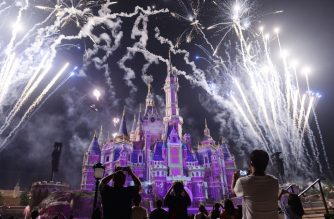 (FILE) This photo taken on June 16, 2017 shows visitors watching fireworks exploding over the castle at an event to mark the first anniversary of the opening of Shanghai Disneyland, in Shanghai. (Photo by STR / AFP)
