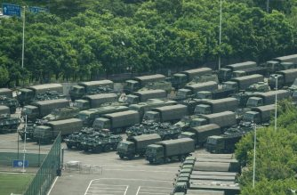 Trucks and armored personnel carriers are seen outside the Shenzhen Bay stadium in Shenzhen, bordering Hong Kong in China's southern Guangdong province, on August 15, 2019. (Photo by STR / AFP)