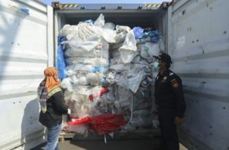 (FILES) This file photo dated July 29, 2019 shows Indonesian officers checking a container full with illegally imported plastic waste in Batam. - Indonesia has sent hundreds of garbage-filled containers back to their countries of origin, according to the customs agency on September 4, 2019, as the Southeast Asian nation pushes back against becoming a dumping ground for foreign trash. (Photo by SEI RATIFA / AFP)