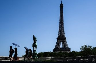 (FILES) In this file photo taken on July 23, 2019 tourist using umbrellas to protect themselves from a scorching sun walk on a bridge over the Seine river in front of the Eiffel Tower in Paris. - In June and July 2019 in France, around 1.500 more people died than usual due to heatwaves, according to a French Ministry of Health study released on September 8, 2019. (Photo by Philippe LOPEZ / AFP)