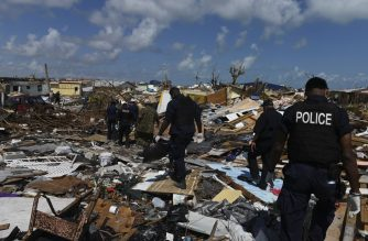 Members of the police join a recovery team looking in the debris in Marsh Harbour, Bahamas, on September 10, 2019, one week after Hurricane Dorian. - Bahamas authorities have updated the death toll from Hurricane Dorian to 50 with the number expected to climb, local media reported, as thousands are evacuated from the archipelago's hardest-hit islands. (Photo by ANDREW CABALLERO-REYNOLDS / AFP)