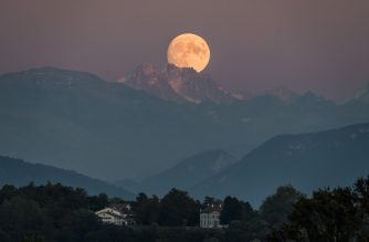 A near full moon rises behind The French Alps as seen from Geneva on September 12, 2019. (Photo by FABRICE COFFRINI / AFP)