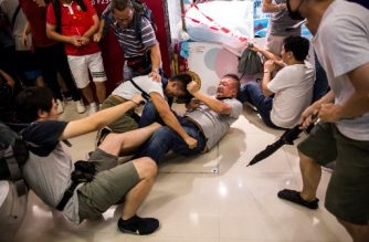 A pro-China supporter (centre R) fights with an anti-government (centre L) protester inside a shopping mall in the Kowloon Bay district of Hong Kong on September 14, 2019. - Millions of people have taken part in demonstrations over the last three months which have morphed into calls for democracy and complaints against the erosion of freedoms under Beijing's rule. (Photo by ISAAC LAWRENCE / AFP)