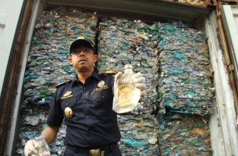 An Indonesia's custom officer shows plastic waste from the container at Jakarta International seaport on September 18, 2019. - Indonesia will ensure that hundreds of containers with rubbish containing hazardous waste are returned to their country. (Photo by DHANY KRISNADY / AFP)