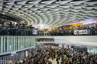 Pro-democracy protesters demonstrate in a shopping mall in the district of Yuen Long to mark the two-month anniversary of the triad attack that took place in the Yuen Long train station, in Hong Kong on September 21, 2019. - Riot police and protesters fought brief skirmishes in a town close to the Chinese border on September 21, the latest clashes during huge pro-democracy protests that have battered the financial hub for more that three months. (Photo by ISAAC LAWRENCE / AFP)