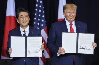 US President Donald Trump and Japanese Prime Minister Shinzo Abe show a trade agreement after it was signed in New York, September 25, 2019, on the sidelines of the United Nations General Assembly. (Photo by SAUL LOEB / AFP)