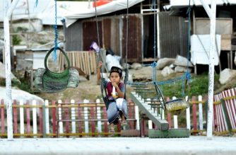 This picture taken on September 25, 2019 shows 9-year-old Rafi Adit Putra sitting on a swing near his living place, a temporary shelter, in Palu, Central Sulawesi, a year after the magnitude 7.5 quake and subsequent deluge razed swathes of the coastal city killing more than 4,300 people and displacing some 170,000 residents. - Indonesia on September 28, 2019 marks one year since a devastating quake-tsunami disaster that pounded the city of Palu, killing more than 4,000 people. (Photo by OLAGONDRONK / AFP) / TO GO WITH: Indonesia-earthquake-tsunami