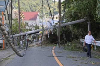 A man walks past a fallen utility pole downed by winds caused by Typhoon Faxai in Kamakura, Kanagawa prefecture on September 9, 2019. (Photo by jiji press / JIJI PRESS / AFP)