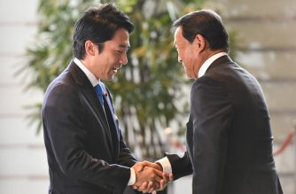 Japan's newly-appointed Environment and Nuclear Disaster Minister Shinjiro Koizumi  (L) shakes hands with Finance and Deputy Prime Minister Taro Aso (R) while arriving at the prime minister's official residence in Tokyo on September 11, 2019.(Photo by Toshifumi KITAMURA / AFP)