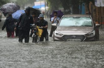 People walk on a flooded road during heavy rain showers in Mumbai on September 4, 2019. (Photo by PUNIT PARANJPE / AFP)
