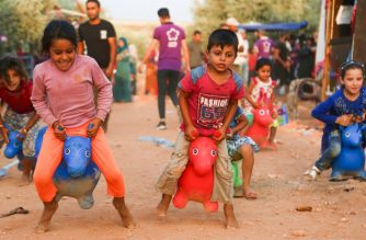 Syrian children who fled battles in the Idlib province and the northern countryside of Hama, participate in games organised by a local association for displaced children at the camp of Al-Sikkah near the town of Kafr Yahmul north of Idlib, on August 14, 2019. (Photo by Zein Al RIFAI / AFP)