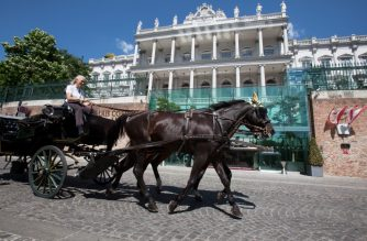 A fiaker passes by the Palais Coburg on June 28, 2019 in Vienna, Austria. (Photo by ALEX HALADA / AFP)