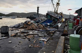 This picture taken on October 1, 2019 shows the wreckage of a fishing boat after a bridge collapsed in the Nanfangao fish harbour in Suao township in Ilan county, eastern Taiwan. - Four bodies have been recovered from under a collapsed bridge in Taiwan, rescuers said on October 2, as searches continued for two people still missing when the structure smashed onto fishing boats moored underneath. (Photo by Sam YEH / AFP)