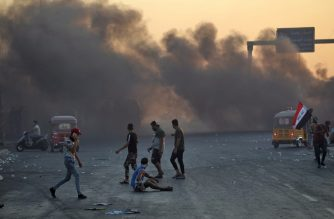 Smoke rises from burning tyres during as Iraqis demonstrate against state corruption, failing public services and unemployment, in the Iraqi capital Baghdad on October 5, 2019. - Renewed protests took place under live fire in Iraq's capital and the country's south Saturday as the government struggled to agree a response to days of rallies that have left nearly 100 dead. The largely spontaneous gatherings of demonstrators -- whose demands have evolved since they began on Tuesday from employment and better services to fundamental government change -- have swelled despite an internet blackout and overtures by the country's elite. Hours after a curfew in Baghdad was lifted on Saturday morning, dozens of protesters rallied around the oil ministry in the capital, facing live rounds fired in their direction, an AFP photographer said. (Photo by AHMAD AL-RUBAYE / AFP)