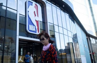 A woman walks past a NBA merchandise store in Beijing on October 8, 2019. - China on October 8 scrapped plans to air NBA exhibition games as the league faced an escalating punishment campaign in the lucrative Chinese market ignited by an American basketball executive's pro-democracy tweet. (Photo by WANG Zhao / AFP)