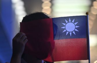A woman holds a Taiwanese flag to cover her face as as she joins others at a rally to mark Taiwan's National Day, in the Tsim Sha Tsui district in Hong Kong on October 10, 2019. - Taiwan's National Day, also called called Double-Ten in a reference to the nationalist Republic of China set up by Sun Yat Sen on October 10, 1911, ending centuries of Chinese dynastic rule. (Photo by Philip FONG / AFP)