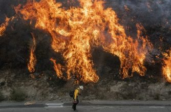 A firefighter walks near a backfire during the Saddleridge fire in Newhall, California on October 11, 2019. - Much of California was on high alert Friday as wind-driven wildfires tore through the state's south, forcing the evacuation of tens of thousands of people and destroying multiple structures and homes. Fire officials said an 89-year-old woman died in Calimesa, about 70 miles (115 kilometers) east of Los Angeles, when fire swept through a trailer park overnight after the driver of a garbage truck that caught fire dumped his burning load nearby. (Photo by Josh Edelson / AFP)