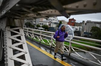 """A pedestrian holds an umbrella as rain falls in Morioka, Iwate prefecture on October 12, 2019, ahead of Typhoon Hagibis' expected landfall in central or eastern Japan later in the evening. - Rated """"large and very strong"""", the storm has already forced the cancellation of two Rugby World Cup matches, disrupted the Suzuka Grand Prix and grounded more than 1,600 flights. (Photo by CHARLY TRIBALLEAU / AFP)"""