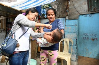A health worker administers polio vaccine on a child during a government-run vaccination drive in Manila on October 14, 2019. - The campaign aims to boost immunisation coverage against the disease to all children five years and below, regardless of their immunisation status. The Philippines on September 2019 detected its first case of polio since 2001. (Photo by Ted ALJIBE / AFP)