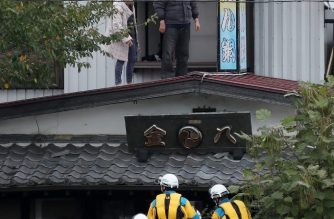 Police officers help residents to evacuate from a flooded area in the aftermath of Typhoon Hagibis in Marumori, Miyagi prefecture on October 14, 2019. - Tens of thousands of rescue workers in Japan battled to find survivors of a powerful typhoon that killed at least 43 people, as fresh rain threatened to hamper efforts. (Photo by JIJI PRESS / AFP) / Japan OUT