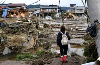 A woman looks at flood-damaged homes in Nagano on October 15, 2019, after Typhoon Hagibis hit Japan on October 12 unleashing high winds, torrential rain and triggered landslides and catastrophic flooding. - Rescuers in Japan worked into a third day on October 15 in an increasingly desperate search for survivors of a powerful typhoon that killed nearly 70 people and caused widespread destruction. (Photo by Kazuhiro NOGI / AFP)
